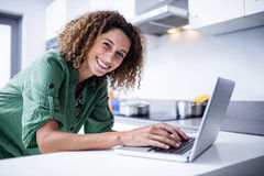 Portrait of woman working on laptop in kitchen Royalty Free Stock Photography