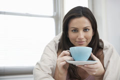 Portrait Of Woman Wrapped With Duvet Drinking Tea Royalty Free Stock Image