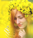 Portrait of a woman with wreath of yellow flowers on the head. Stock Photo