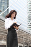 Portrait woman write massage on her book with behind modern buil Stock Image