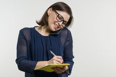 Portrait of woman writes on a notebook and calling phone stock photography