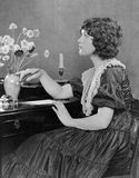 Portrait of woman writing at desk Stock Photos