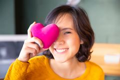 Portrait of woman in yellow sweater holding pink heart. peop royalty free stock photo