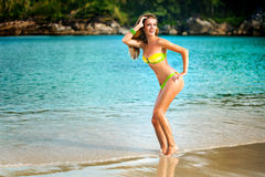 Portrait of woman in yellow swim posing on tropical beach. Young pretty hot woman on the tropic island in summer near the sea. Young caucasian woman near ocean stock photography