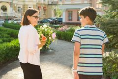 Portrait of woman with bouquets of flowers and teenage boy on city background. Son congratulated his mother. Portrait of women with bouquets of flowers and Stock Photo