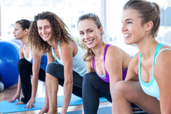 Portrait of women doing high lunge pose in fitness studio Stock Images