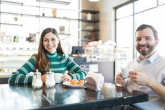 Couple Spending Leisure Time In Cafe. Portrait of women and men smiling while drinking fresh coffee in bakery royalty free stock image