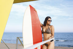 Portrait of a women in swimsuit holding surfboard with copy space for your brand while preparing for swimming Royalty Free Stock Photos