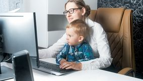 Portrait of young woman working from home office with her toddler son. Portrait of women working from home office with her toddler son Royalty Free Stock Image