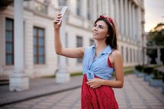 Portrait of wonderful caucasian woman taking selfie with smartphone in Europe. Brunette female hipster with piercing in Stock Photography