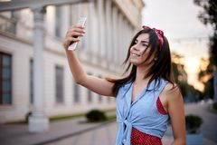 Portrait of wonderful caucasian woman taking selfie with smartphone in Europe. Brunette female hipster with piercing in Stock Images