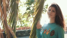 Stunning girl on vacation on sea. Portrait of wonderful smiling woman in a blue sweater posing under palm tree alone. Attractive redhaired woman outside stock video footage