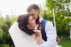 Bearded groom kissing his bride cheek outdoor. Portrait of wonderful young just married couple in love at nature background Royalty Free Stock Images