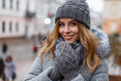 Portrait of a wonderful young woman with beautiful blue eyes with natural make-up in a sweet smile in a knitted hat. In knitted mittens in a stylish coat on the royalty free stock image