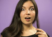 Portrait of a Wondering Charming Brunette girl on a Purple Background Stock Image