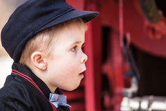 Portrait of Wondering Preschool Child. Portrait of an amazed little child boy wearing vintage school clothing uniform with hat and bow tie Royalty Free Stock Photo