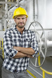 Portrait of worker with arms crossed leaning on large valve in industry Royalty Free Stock Photos