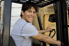 Portrait Of A Worker Driving Forktruck. Portrait of a happy male worker driving forktruck in the warehouse Royalty Free Stock Photography