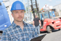 Portrait worker in hardhat holding clipboard. Portrait of worker in hardhat holding clipboard Royalty Free Stock Image