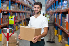 Portrait of worker is holding cardboard boxes and smiling to the camera. In a warehouse Stock Image