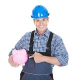 Portrait Of A Worker Holding Piggybank Royalty Free Stock Photography