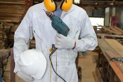 Portrait of worker with safety uniform holding electric drill in carpentry workshop. Royalty Free Stock Photography