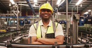 Portrait of worker standing with arms crossed near production line. In bottle factory stock video footage