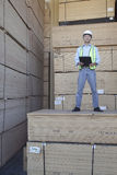 Portrait of a worker standing on stack of plywood Stock Image