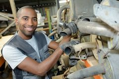 Portrait worker with used vehicle silencers Stock Photography