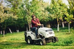 Portrait of worker using lawn mower for cutting grass. Portrait of industrial worker using lawn mower for cutting grass Royalty Free Stock Photo