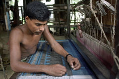 Portrait of working weaver in weaving mill. BANGLADESH: this Bangladeshi man sits behind a loom in a weaving factory in the village Tangail. He is knotting Royalty Free Stock Images