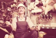 Portrait of workman choosing soft roller. Portrait of workman in uniform choosing soft roller for painting in housewares hypermarket Royalty Free Stock Photo