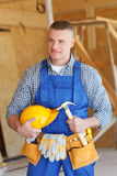 Portrait of workman. With hammer and helmet Stock Image