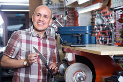 Portrait of workman sharpening steel knife on  wheel lathe Royalty Free Stock Images