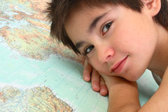 Portrait with world map. Tranquil boy looking at the camera with map background Stock Photo
