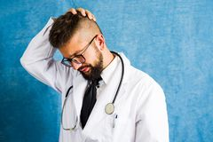Portrait of a worried doctor against blue background Royalty Free Stock Image