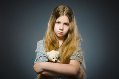 Portrait of worried girl playing with teddy bear isolated on gray Stock Images