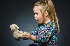 Portrait of worried girl playing with teddy bear isolated on gray Stock Image