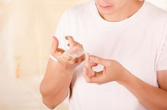 Portrait of worried man holding an open broken condom with one hand in front of his face and touching the broken piece Stock Image