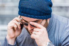 Portrait of a worried man with sunglasses talking on the phone - close up view Royalty Free Stock Photo