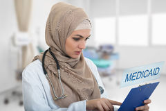 Portrait of worried muslim female Medical doctor holding paperclip in hospital. Medicaid sign Royalty Free Stock Images