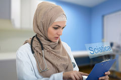 Portrait of worried muslim female Medical doctor holding paperclip in hospital. SCIATICA Royalty Free Stock Photos