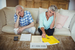 Portrait of worried senior couple checking bills in living room Royalty Free Stock Images