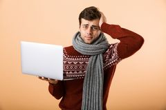 Portrait a worried sick man dressed in sweater. And scarf isolated over beige background, browsing, holding laptop computer royalty free stock photography