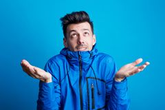 Portrait of a worried young man in a studio with anorak on a blue background. Portrait of a worried young man in a studio with anorak, throwing his hands up in stock photo