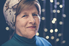 Portrait of a wrinkled face kind grandmother in a headscarf with bokeh Stock Photos