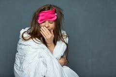 Portrait of yawning woman with blanket. Sleep disorders concept Stock Image