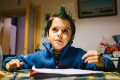 Portrait of 9 year old baby boy with crest of green colored hair. Portrait of 9 year old boy at home with crest of green colored hair Royalty Free Stock Images