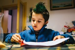 Portrait of 9 year old baby boy with crest of green colored hair. Portrait of 9 year old boy at home with crest of green colored hair Stock Images
