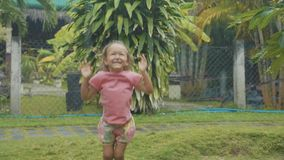 Portrait 5 year old child girl having fun during a tropical rain, slow motion. Portrait 5 year old child girl having fun during a tropical rain in slow motion stock footage
